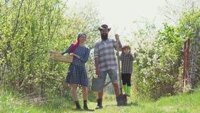 Familjbondebegrepp lycklig familj Lyckliga familjbönder som arbetar med potatis på vårfält Eco semesterortaktiviteter arkivfilmer
