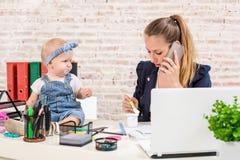 Familjeföretag - telecommute affärskvinnan, och modern med ungen gör en påringning royaltyfri foto