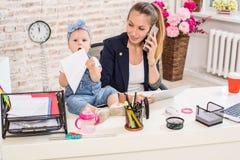 Familjeföretag - telecommute affärskvinnan, och modern med ungen gör en påringning arkivfoton