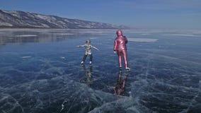 Familjen är skridskoåkningen på dagen Flickor som rider diagramet isskridskor i natur Moder, dotter och son som tillsammans rider stock video