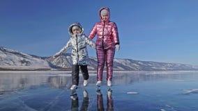 Familjen är skridskoåkningen på dagen Flickor som rider diagramet isskridskor i natur Moder och dotter som tillsammans in rider p lager videofilmer