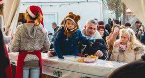 Familjen äter chiper i ett litet marknadstält Royaltyfri Foto