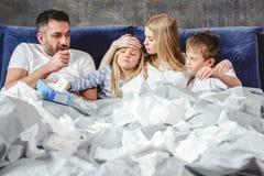 Familjen av fyra har en rökkanal och att ligga på säng arkivbilder