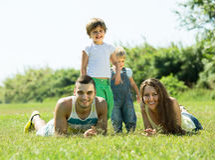 Familjen av fyra i gräs på parkerar Arkivfoto