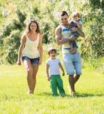 Familjen av fyra i soligt parkerar Arkivfoto