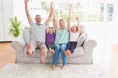Familjen av fyra med armar lyftte sammanträde på soffan Fotografering för Bildbyråer