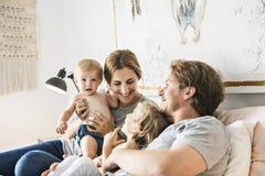 Familjen av fyra med behandla som ett barn ha gyckel på säng royaltyfri fotografi