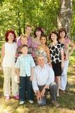Familjen av nio folk poserar på parken Royaltyfri Fotografi