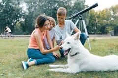 Familjen av tre barn går i parkerar med den skrovliga vita hunden och att sitta på gräsmattan och att ha gyckel som ser mobiltele royaltyfria foton