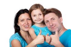 Familjen av tre ger upp deras tum. Arkivbild