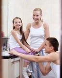 Familjen av tre personer borstar deras bucklor Arkivbilder