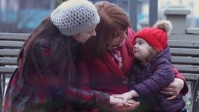 Familjen av tre utvecklingar av att le kvinnor som sitter på en bänk i staden, parkerar och att omfamna bolts muttrar för sammans stock video