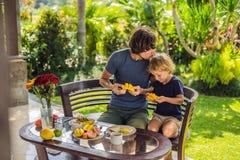 Familjen av två som utmärkt äter, tjänade som frukosten utanför den stiliga unga mannen som häller något kaffe och hans gulliga ä arkivfoto