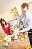 Familjen bakar kakor Arkivbild