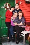 Familjen består modern, farmodern, farfadern, sonson i rummet som dekoreras för jul royaltyfri fotografi