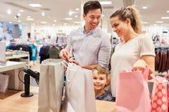 Familjen betalar kassa på checkout royaltyfri foto
