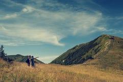 Familjen diskuterar om resplan på överkanten av berghil Royaltyfria Foton