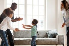 Familjen för det blandade loppet har gyckel som hemma spelar leken royaltyfri foto