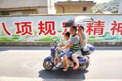Familjen för tre person rider en sparkcykel med paraplyet som skyddar från solen Royaltyfria Bilder