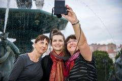 Familjen för tre utveckling av handelsresande stoppar för selfie royaltyfria foton