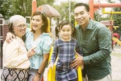 Familjen för tre utveckling ser lycklig i lekplats fotografering för bildbyråer