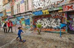 Familjen förbigår bländande gatakonst på Rue Denoyez i Paris royaltyfri foto