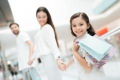 Familjen, fadern, modern och dottern går från ett lager till andra i shoppinggalleria fotografering för bildbyråer