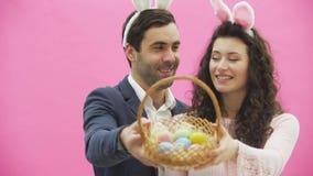 Familjen firar påskdag Lyckliga par med kaninöron lyckliga ferier Koppla ihop målningägg för påsk dekorera arkivfilmer