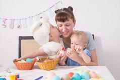 Familjen firar påskhögtiden: Mamman målar en modell på påskägget Sonen kysser hans moder på kinden fotografering för bildbyråer