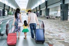 Familjen går i flygplatskorridor royaltyfri fotografi