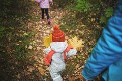 Familjen går i hösten barn promenerar banan som beströs med sidor royaltyfri fotografi