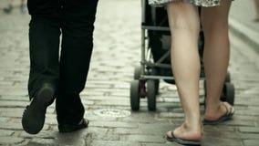 Familjen går med behandla som ett barn sittvagnen på kullerstentrottoar stock video