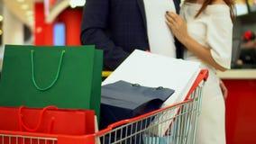 Familjen går på handelgalleria Den stora lagervagnen med mång--färgade packar av gåvor i köpcentrum mot stock video