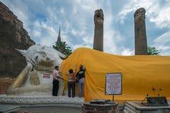 Familjen ger ämbetsdräkten till att vila buddha, Wat Yai Chai Mongkol Royaltyfria Bilder
