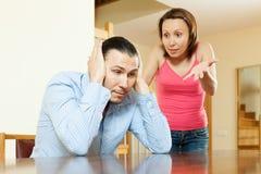 Familjen grälar. Trött man som lyssnar till hans ilskna fru Arkivfoto