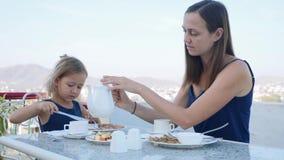Familjen har en frukost tillsammans på terrass med härlig bergsikt lager videofilmer