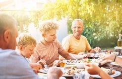 Familjen har en matställe på öppen luft i sommarträdgård arkivbild