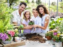 Familjen har gyckel i arbetet av att arbeta i trädgården Royaltyfri Bild