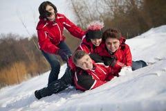 Familjen har gyckel i snön Royaltyfri Foto
