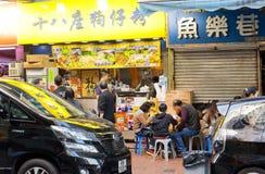 Familjen har matställen i liten kinesisk snabbmatsrestaurang med den traditionella menyn Arkivfoto