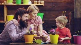 Familjen har roliga ordnande och bevattna blommor isolerad skyddswhite för begrepp 3d bild Hjälpmoder och fader för litet barn so stock video