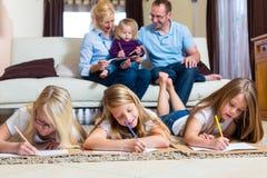 Familjen hemma, barnen som färgar på, däckar Royaltyfri Fotografi