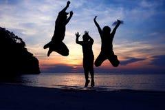 Familjen hoppade på stranden med solnedgånghimmel Arkivbild