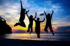 Familjen hoppade på stranden med solnedgånghimmel Arkivfoton