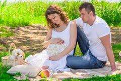 Familjen i förväntan av ett barn, vilar nära en sjö Royaltyfri Fotografi