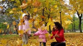 Familjen i höst parkerar kastar upp sidor Mamman och två döttrar spelar med sidor i parkera i nedgången Härlig guling stock video