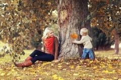 Familjen i höst parkerar! Lycklig moder och barn som har gyckel Arkivbilder