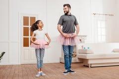 Familjen i rosa ballerinakjoltyll kringgår att dansa hemma Royaltyfri Bild