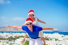 Familjen i Santa Hats tycker om grekisk semester med härlig sikt Royaltyfri Bild
