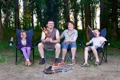 Familjen i skog på picknick, gör grillfesten, kött som lagas mat på brand, träd på bakgrund fotografering för bildbyråer